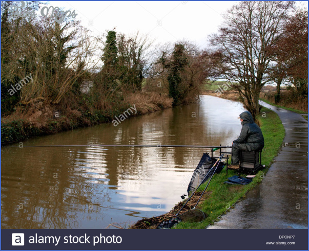man fishing on the bude canal on a wet winter day cornwall uk dpcnp7 Winter Canal Fishing