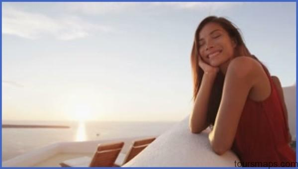 oia sunset on santorini and woman tourist smiling pretty lady enjoying caldera sunset view from resort relaxed female is on vacation travel holiday on the famous greek island in greece europe rtdehtqa FEMALE TRAVEL QA LADIES, YOU NEED TO KNOW THIS